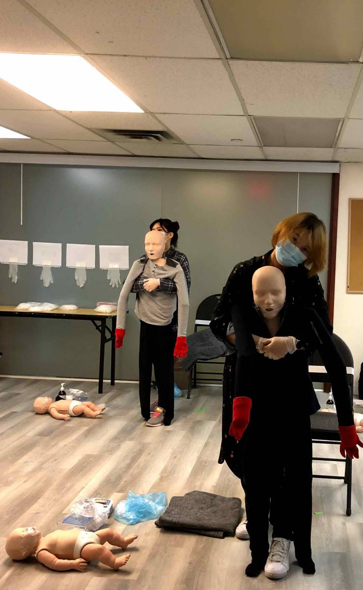 Students learning CPR with full body manikins